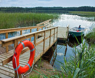 Boat with a wooden pier  on the lake Stock Photography