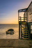 Boat and Wooden Stairs by the Sea during Sunset Stock Photos
