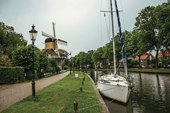 Boat and wooden yellow windmill next to wide tree-lined canal under cloudy sky at sunset in Weesp. Quiet and pleasant village full of canals and green near Stock Photo