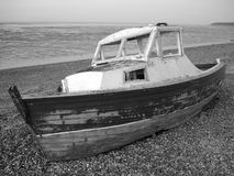 Boat wreck on the beach. Decaying weather-beaten boat wreck left on the beach Stock Photography
