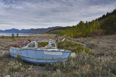 Boat wreck. Old abandoned wooden boat wreck with peeling blue paint on the shore Stock Images