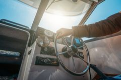 Boat or yacht captain hand on boat steering wheel and sea navigation system. Close up stock photos