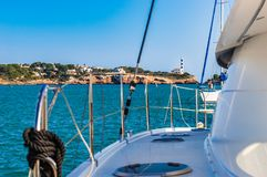 Boat yacht deck with view of lighthouse in Porto Colom at coast of Majorca, Spain. Idyllic view of lighthouse in Porto Colom from marina, Mallorca island, Spain Royalty Free Stock Photo