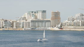 Boat ,Yacht sails in the background of city Valletta in Malta. Wide shot, in the background of newly constructed houses. Boat ,Yacht sails in the background of stock footage