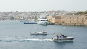 Boat ,Yacht sails in the background of city Valletta in Malta. Wide shot, in the background of newly constructed houses. Bypass yachts in Valletta Bay Malta. In stock footage
