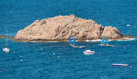 Boat and yachts near tiny island at sea Stock Photography