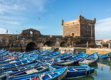 Fishing Boats and fishermen with fortress at the harbor in Essaouira, Morocco Stock Photos
