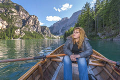 In the boat. Young woman with oars at the picturesque lake. The Dolomite Alps. Italy Stock Photos