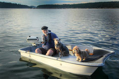 Boater with dogs on small boat. A closeup of an older scruffy man wearing a wool captains bill cap, glasses and a life jacket on the water running a small Royalty Free Stock Photography