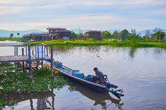 The boater in Kayak, Inle Lake, Myanmar. YWAMA, MYANMAR - FEBRUARY 18, 2018: The boater waits the tourists, siting in kayak, moored in wharf of Nga Phe Chaung Royalty Free Stock Image