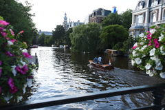 Boaters on an Amsterdam canal seen from a bridge lined with flowers. A view from a flower-lined bridge of boaters on a leisurely ride on an Amsterdam canal Stock Photography