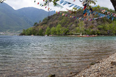 Boaters on Clear Lake. Boats ride past a small island at Lugu Lake in Yunnan province, China Royalty Free Stock Image