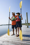 Boaters on dock. African American middle-aged couple standing on boat dock holding paddles wearing life preservers Stock Images