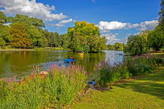 Boaters on lake in park, Birmingham, England Stock Images