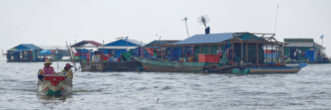 Boaters near huts of Tonle Sap, Cambodia Stock Photo