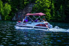 Free Boaters On Pontoon Boat Enjoy Summer Day On Lake Placid In New York State`s Adirondack Mountains Stock Image - 197274741