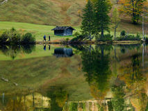 Boathouse in Bavarian Alps. Small mountain lake with boathouse on the other side, and hikers walking along by; late summer scene with many shades of green and a Royalty Free Stock Image