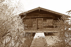 Boathouse with boardwalk and shrubbery, sepia colored Royalty Free Stock Photography
