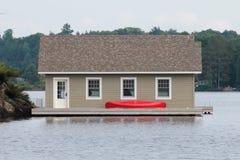 Boathouse con una canoa roja imagen de archivo
