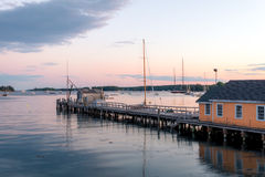Boathouse and dock in the harbor at dusk. Boothbay Harbor boathouse and dock reflected in the water at dusk Stock Image