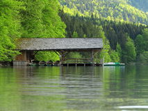 Boat shed at mountain lake by spring. Idyllic scenery at spring with a boat shed on the calm waters of a lake. Landscape idyll in Germany Royalty Free Stock Image