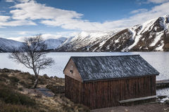 Boathouse and Mountains in Winter at Loch Muick in Scotland. Royalty Free Stock Images