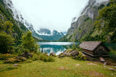 A boathouse near a Lake surrounded by mountains and mist in Bavaria, Germany. Stock Photography