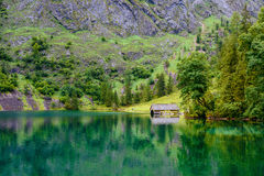 A boathouse near a Lake surrounded by mountains and trees in Bavaria, Germany. Royalty Free Stock Photo