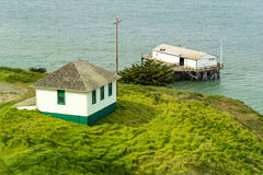 Boathouse on a pier next to small house. Small house on a bluff with a boathouse on a pier Royalty Free Stock Photos