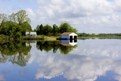 Boathouse reflected in river stock image