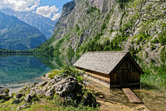Old boathouse in scenic alpine landscape. An old boathouse in mountainous landscape at a lake of the Alps Stock Images