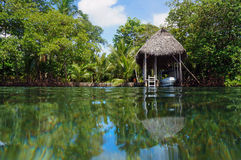 Boathouse with tropical vegetation. Boathouse with palm roof and lush tropical vegetation reflected on water surface, Bocas del Toro, Caribbean sea, Central Royalty Free Stock Photo