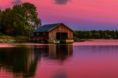 Boathouse on waters at sunset. Boathouse on shore with pink skies reflected in waters at sunrise or sunset royalty free stock image