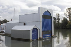 Boathouses. Two boathouses used for storing boats on a river Royalty Free Stock Photo