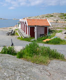 Boathouses close to the sea. With water and cliffs in the background Royalty Free Stock Photos