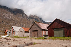 The boathouses at the fjord coast and clouds. The horizontal picture of the oldfashined boathouses at the fjord coast and clouds royalty free stock image
