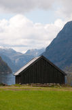 The boathut in the fjords. The vertical picture of the oldfashined boathouse at the norwegian fjord coast line stock images