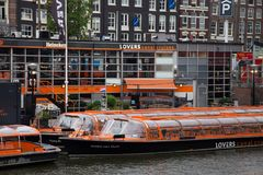 AMSTERDAM, NETHERLANDS - JUNE 25, 2017: Orange boats of the Canal Lovers Cruises. Boating along the canals of Amsterdam is one of the popular types of tourist Stock Image