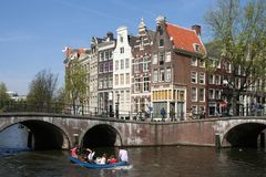 Boating in Amsterdam. People boating in an Amsterdam canal stock photos