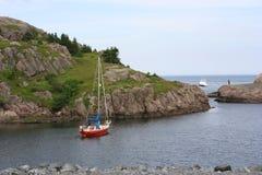 Boating around the coast. A small sail boat sails along a rocky coast Royalty Free Stock Photos