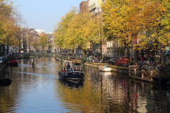 Boating in autumn in Amsterdam canal, Holland Royalty Free Stock Photos