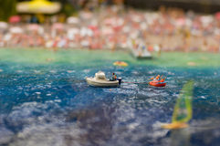 Boating on the beach. People drive a boat in the summer beach miniature Stock Image