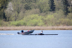 Coach and Woman Sculling in Burnaby Lake. A woman practicing the sport of one man sculling in her shell, with a coach nearby giving encouragement and guidance Royalty Free Stock Images