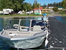 Boating and camping scenic. Focusing on the boat to lead to view behind it; a view from the wharf at the lake Stock Images