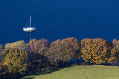 Boating on the Coniston Water, Lake District, UK. Boat on a still Coniston Water in Autumn (Fall). Taken from a high vantage point in Grisedale Forest to the Royalty Free Stock Images