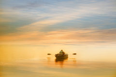 Boating in the dawn. Lonely man boating in the dawn Stock Image