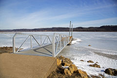 A boating dock at sunrise on a frozen lake. A boating dock sits frozen in a lake at sunrise Stock Photography