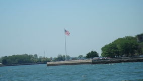 Boating by Ellis Island and Statue of Liberty stock footage
