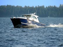 Boating on the lake. A boat moves along a lake on a nice day Stock Image