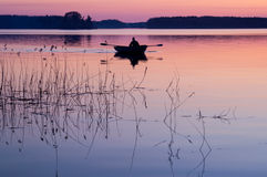 Boating. Man swimming in a boat at sunset Stock Photos